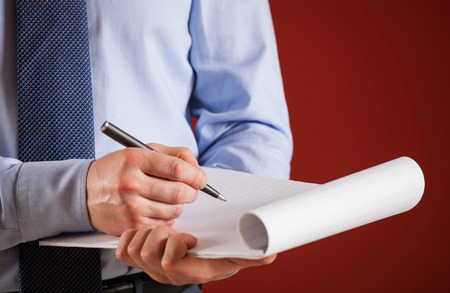 businessman signing documents: Businessman signing documents, red background