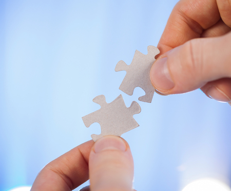 puzzlement: Human hands holding details of puzzle, blue background Stock Photo