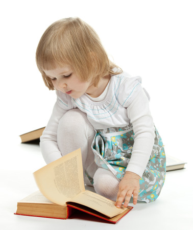 turning page: The little girl sitting on the floor and turning over a page; white background Stock Photo