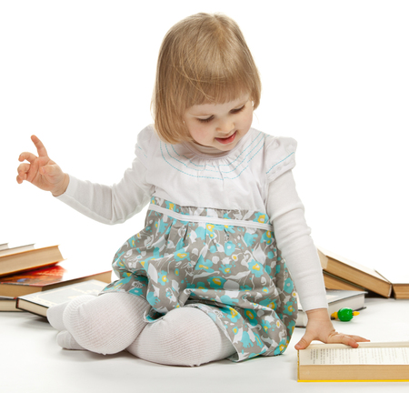 children clothing: The little girl sitting among books and turning over the pages; white background