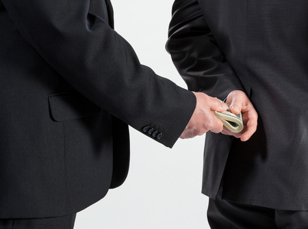 corruptible: Businessman giving a bribe, neutral background Stock Photo