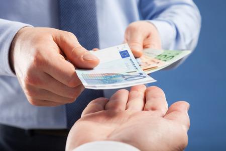 Mani dell'uomo d'affari lo scambio di euro su sfondo blu, girato in primo piano
