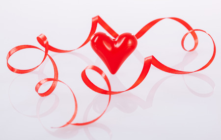twisted: Twisted red ribbon and ceramic heart on neutral background