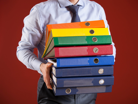 solid background: Businessman giving folders to you, closeup shot