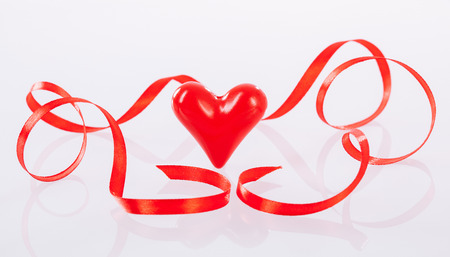 ceramic heart: Twisted red ribbon and ceramic heart on neutral background