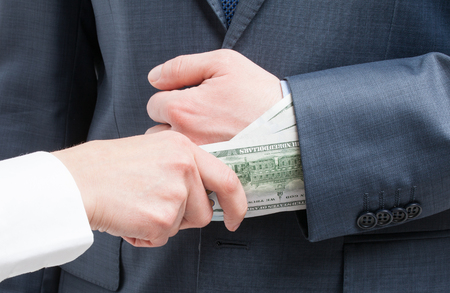 venality: Giving a bribe into a sleeve - closeup shot