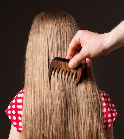 Male hand combing beautiful long hair, closeup shot