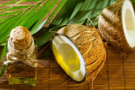 aceite de coco: Aceite, coco y rama verde sobre fondo de paja - hermoso balneario, cuidado del cabello y cuidado de la piel composición en la luz de la mañana