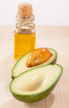 haircare: Sliced avocado and a bottle of oil on wooden table- spa, bodycare and haircare concept