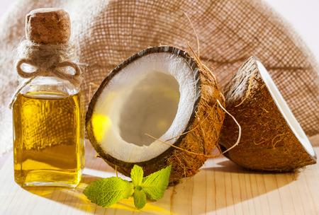新鮮なココナッツ、木製のテーブル - 美しいスキンケアとヘアケア成分の油とミントの葉のボトル