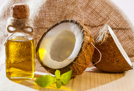massage huile: noix de coco fraîche, bouteille d'huile et une feuille de menthe sur la table en bois - belle soin et composition capillaire Banque d'images