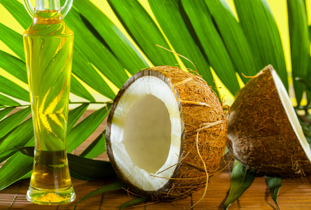 haircare: Cracked coconut and a bottle of oil on the table - spa, skincare, haircare and relaxation concept