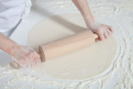 cook out: Female cook rolling out dough on  the table, closeup shot Stock Photo