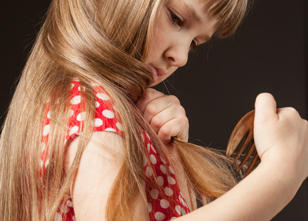 Little girl combing her beautiful long hair, black background