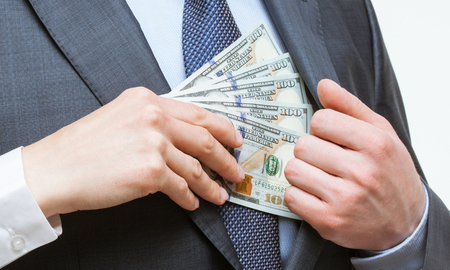corruptible: Giving a bribe into a pocket - closeup shot Stock Photo