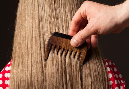 niños rubios: Mano masculina que peina el pelo largo y hermoso, tiro del primer Foto de archivo
