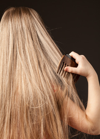 combing: Little girl combing her beautiful long hair, black background