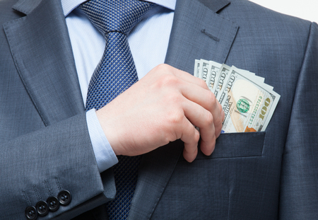 Businessman putting money in the breast pocket, closeup shot Stock Photo