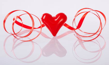 twiddle: Twisted red ribbon and ceramic heart on neutral background