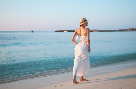 Happy young woman in a white sundress walking by the beach