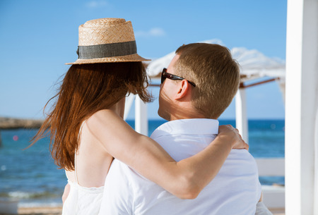gentle dream vacation: Happy young couple resting near the sea and  looking each other