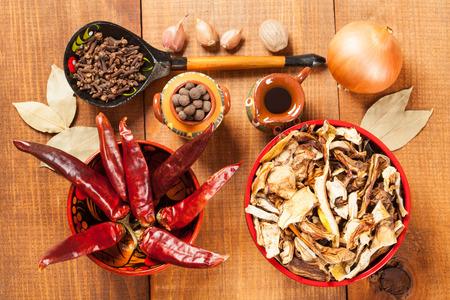 legumbres secas: Los hongos secos y pimientos rojos y otras verduras y especias, tiro del primer, fondo de madera Foto de archivo