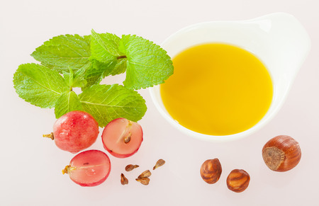 haircare: Haircare and skincare composition: mint leaves, grapes, nuts and natural oil on neutral background