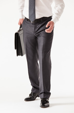 businesslike: Unrecognizable young businessman holding  a briefcase , white background