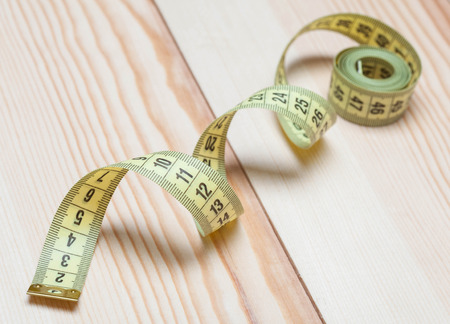 wooden metre: Yellow tape measure on wooden background