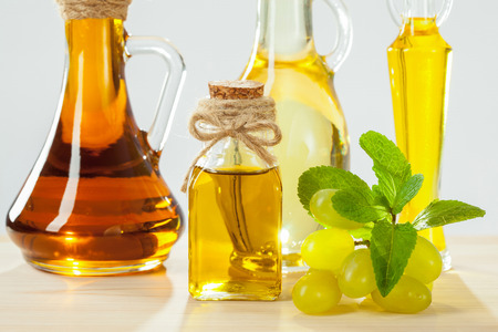 Belle soin et composition capillaire: bouteilles d'huiles naturelles, des raisins et des feuilles de menthe sur table en bois Banque d'images