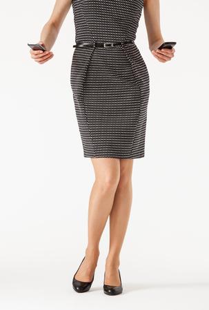 businesswoman legs: Unrecognizable businesswoman  holding two cellphones , white background
