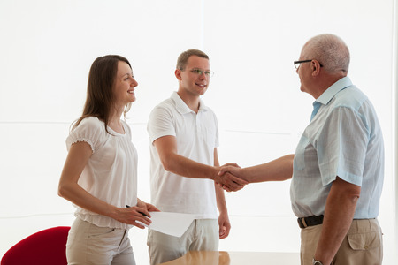 Successful business people shaking hands while making agreement photo