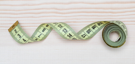 cintas metricas: Yellow tape measure on wooden background