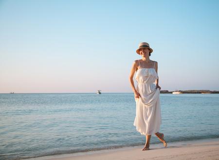 sundress: Beautiful young woman in a white sundress walking along seashore Stock Photo