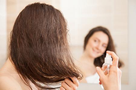 wet: mujer joven de aplicar la laca para el pelo delante de un espejo sonriendo; concepto de cuidado del cabello Foto de archivo