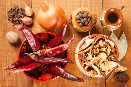 dried vegetables: Dried mushrooms and red peppers and other vegetables and spice, closeup shot, wooden background Foto de archivo