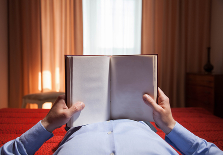 informal clothing: Man holding opened book at home - closeup shot