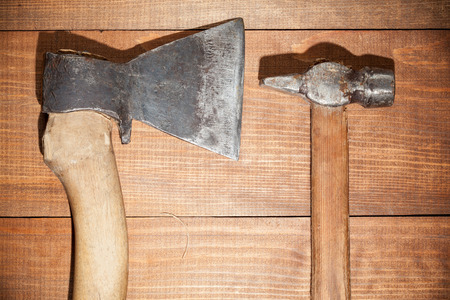 acuminate: Ax and hammer on wooden background