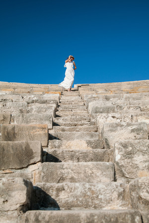 sundress: Beautiful young woman in a white sundress and in a straw hat standing on the top  of stone stairs Stock Photo