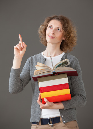 Smiling young woman holding books, gray background photo