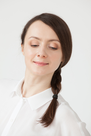 unworried: Portrait of a smiling young woman, white background Stock Photo