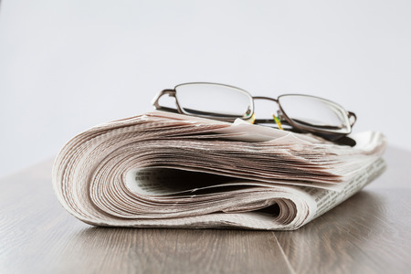 Free newspaper and glasses on the table, closeup shot