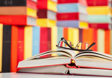 classics: Opened book and glasses on colored background - closeup shot