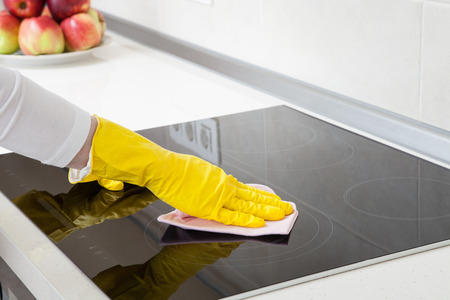 induction: Housewife cleaning an induction plate, closeup shot