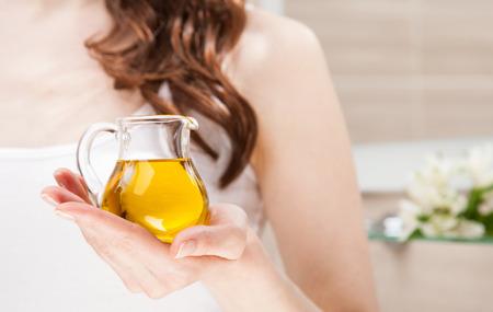 massage huile: Unrecognizable femme tenant pot de verre avec de l'huile d'olive vierge - soins de la peau et le concept de haircare Banque d'images