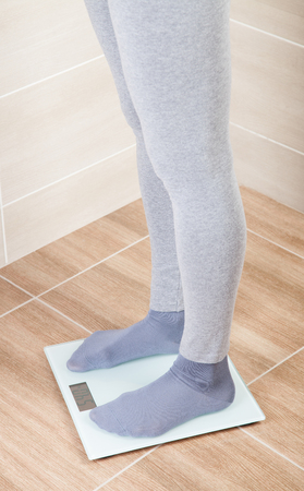weigher: Unrecognizable young woman standing on the scales and measuring her weigh, closeup shot