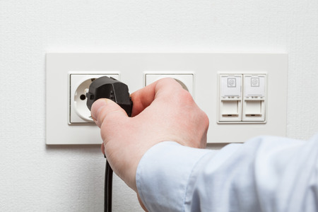 plug in: Male hand puts plug in the socket, closeup shot Stock Photo