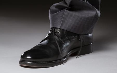 satined: Male leg in black leather shoe - closeup shot Stock Photo