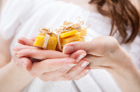 beeswax candle: Unrecognizable womans hands holding pieces of natural beeswax, packed and decorated