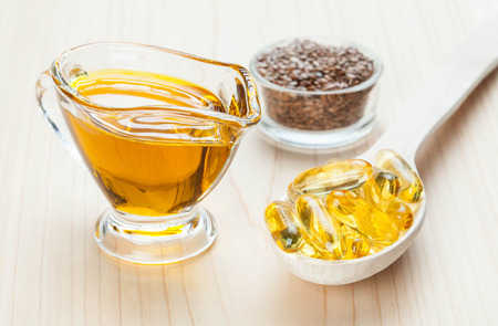 Small glass jug of flax oil, bowl with flax seeds and wooden spoon with fish oil capsules. Sources of Omega-3 for healthy hair, skin and nails.